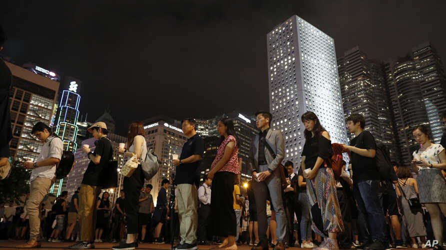 Attendees hold candles in a vigil for the fourth apparent suicide related to the protests against an extradition law to China, in Hong Kong, July 10, 2019.