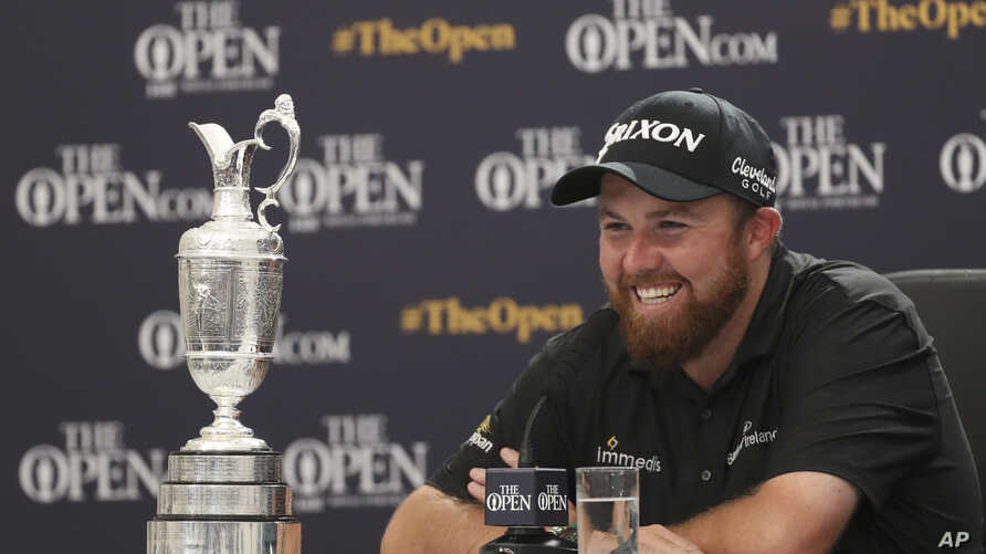 Ireland's Shane Lowry smiles as he sits next to the Claret Jug trophy at a press conference after winning the British Open Golf Championships, at Royal Portrush in Northern Ireland, July 21, 2019.