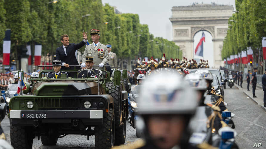 France's President Emmanuel Macron gestures in his command car next to French Armies Chief Staff General Francois Lecointre as they review troops before the start of the Bastille Day military parade down the Champs-Elysees avenue in Paris, July 14, 2019.