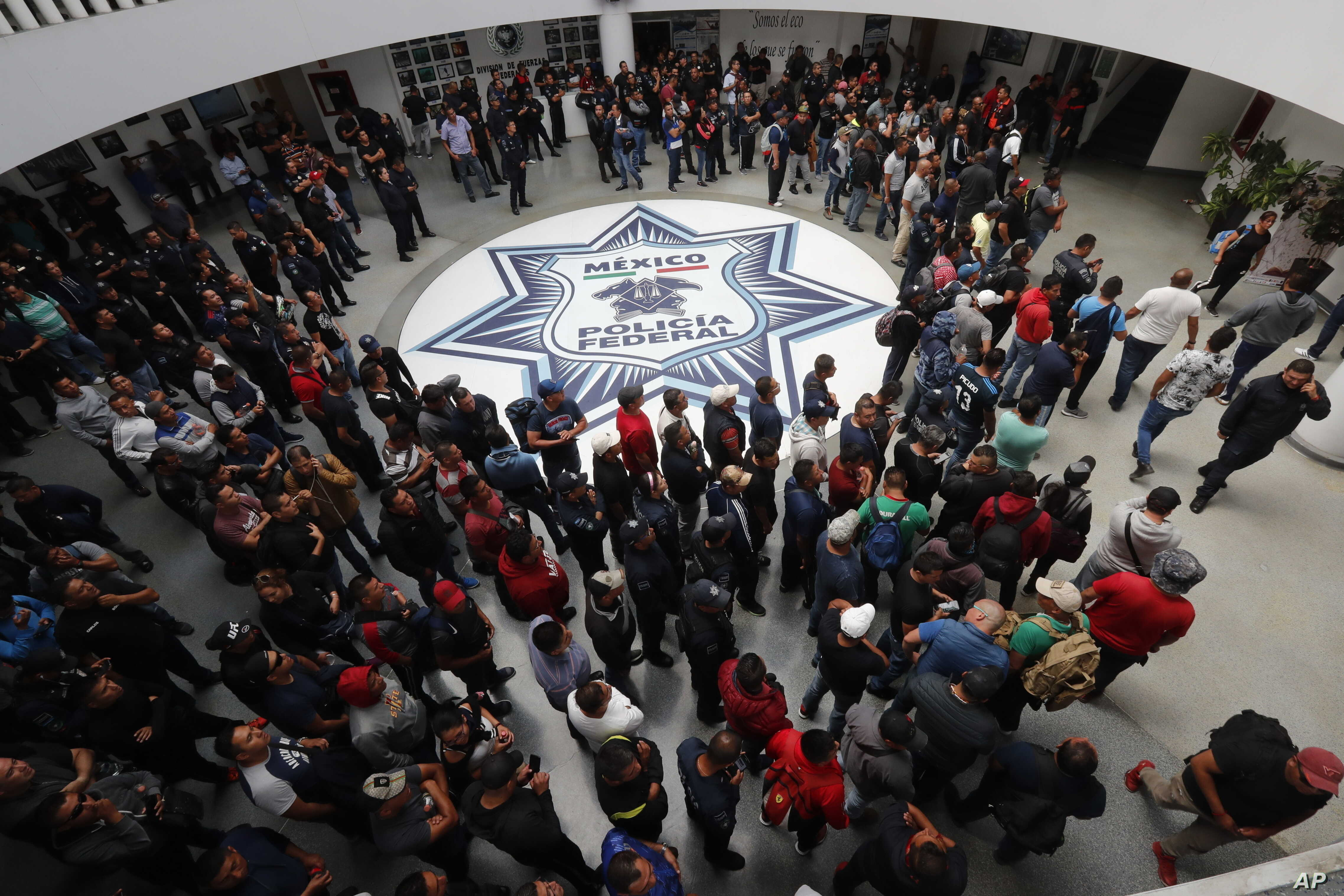 FILE - Dozens of Mexican federal police gather at a police command center in the Iztapalapa borough, in Mexico City, to protest against plans to force them into the newly formed National Guard, July 3, 2019.
