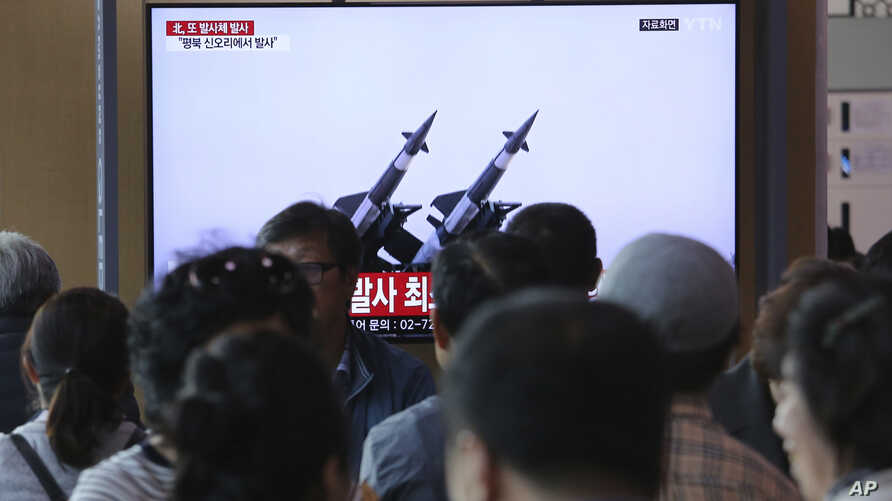 People watch a TV broadcast showing file footage of North Korean missiles, during a news program at the Seoul Railway Station, in Seoul, South Korea, May 9, 2019.