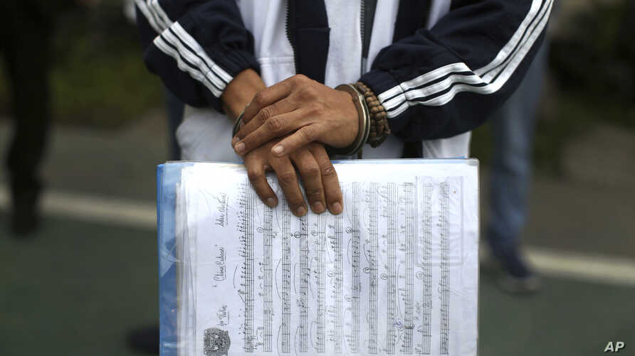 A handcuffed inmate holds a sheet of music in a prison courtyard in Callao, Peru, as he waits to be transported to a classical music session with a symphony orchestra in the national theater in the Peruvian capital, July 19, 2019.