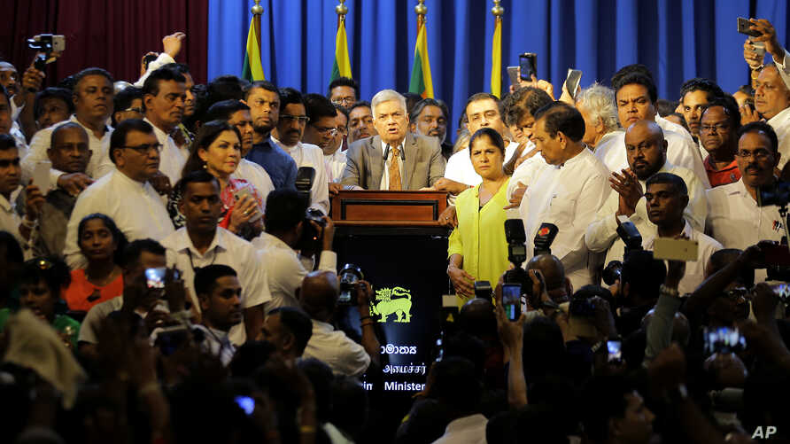 FILE - Sri Lanka's reinstated Prime Minister Ranil Wickeremesinghe, center, surrounded by his loyal lawmakers and supporters speaks after assuming duties in Colombo, Dec. 16,2018.