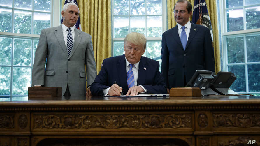 President Donald Trump, joined by Vice President Mike Pence, left, and Secretary of Health and Human Services Alex Azar, right, signs a $4.6 billion aid package at the White House, July 1, 2019.
