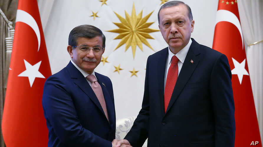 FILE - Turkish President Recep Tayyip Erdogan, right, and Prime Minister Ahmet Davutoglu shake hands as they pose for a photograph during a final farewell in Ankara, May 19, 2016.