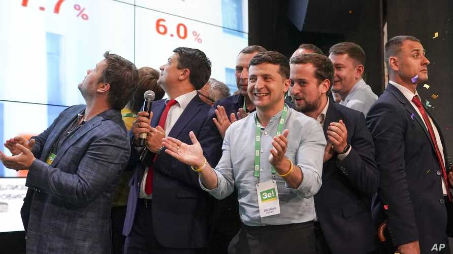 Ukrainian President Volodymyr Zelenskiy, center, applauds with his team as they look at election results at his party's headquarters after a parliamentary elections in Kyiv, Ukraine, July 21, 2019.
