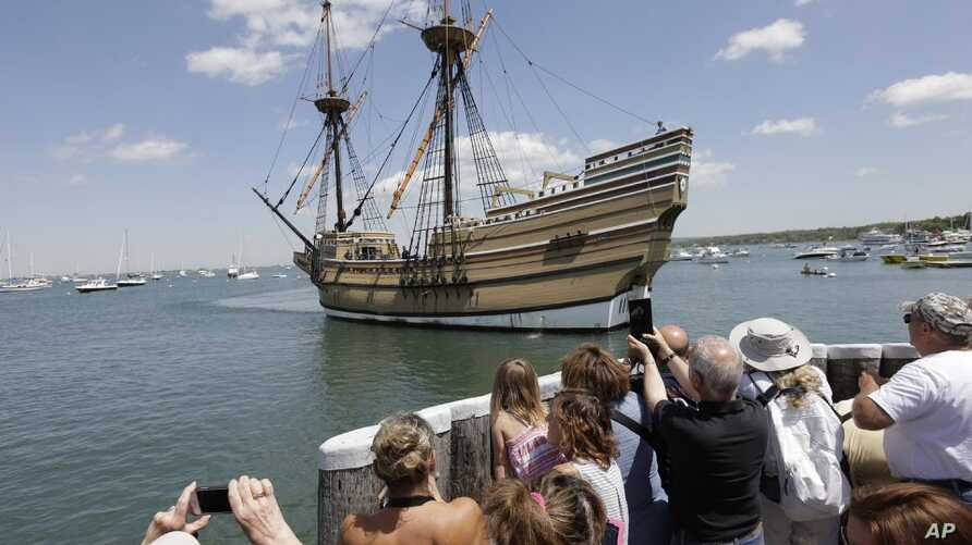 FILE - People on a wharf watch as the Mayflower II, the 1957 replica of the famed ship that carried the Pilgrims to Massachusetts in 1620, as it arrives in Plymouth Harbor in Plymouth, Mass., June 2, 2016.