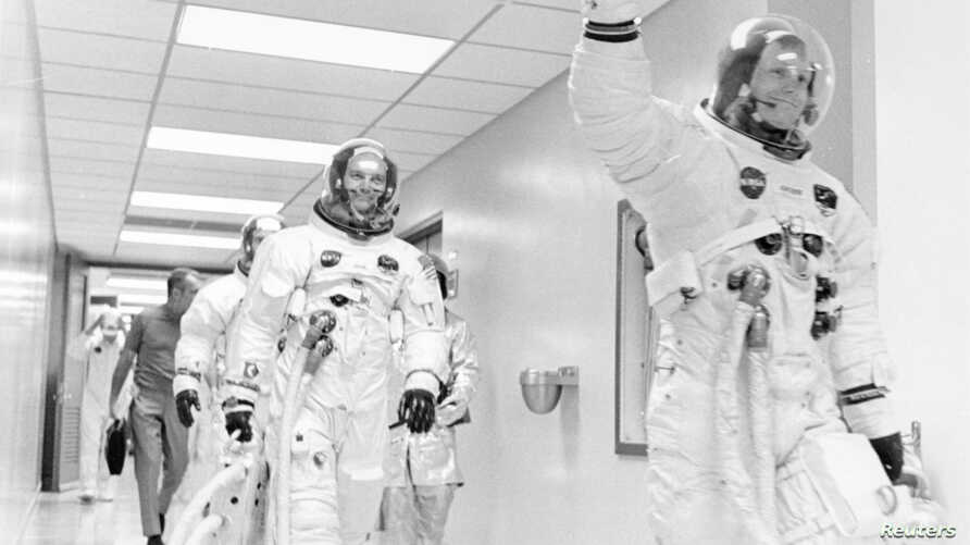 Apollo 11 astronaut Neil Armstrong waves to well-wishers on the way out to the transfer van, Cape Canaveral, Florida, July 16, 1969. Mike Collins and Buzz Aldrin follow Armstrong down the hallway.