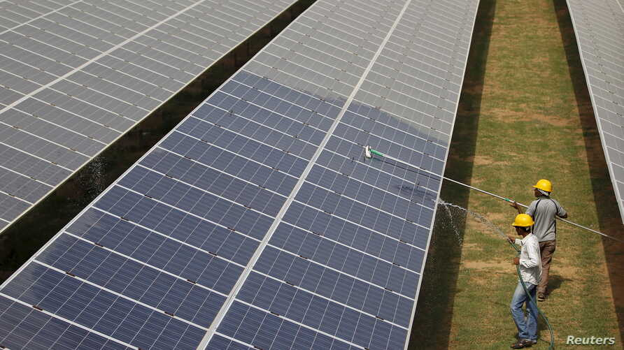 Workers clean photovoltaic panels at a solar power plant in Gujarat, India, July 2, 2015.