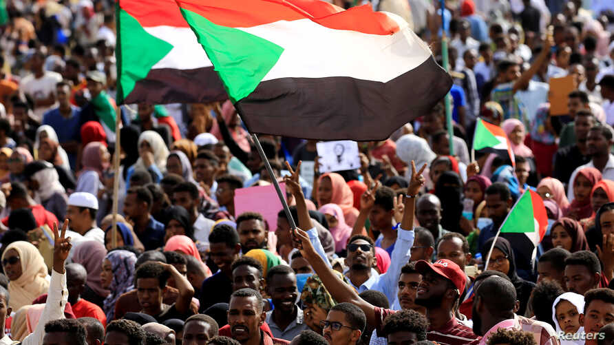 Sudanese protesters and wave flags during a rally at the Green Square in Khartoum, Sudan, July 18, 2019.