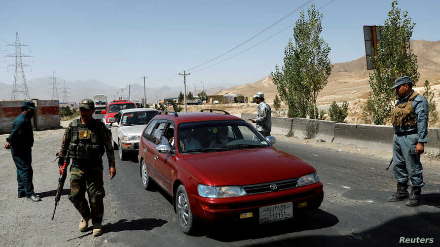 Afghan security forces keep watch at a checkpoint on the Ghazni highway, in Maidan Shar, the capital of Wardak province, Aug. 12, 2018.