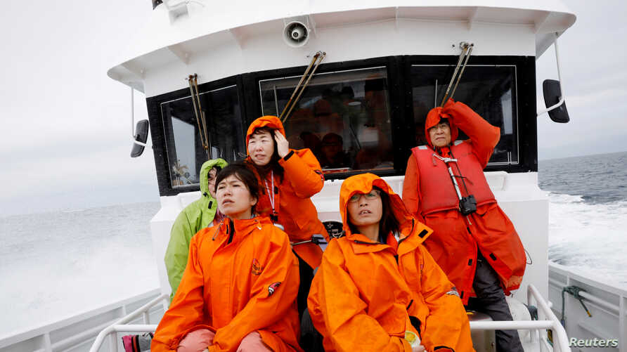 Tourists on a whale watching tour boat look for whales in the sea near Rausu, Hokkaido, Japan, July 1, 2019.