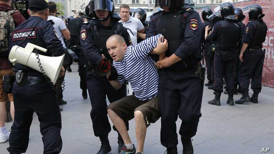 Police officers detain a man during an unsanctioned rally in the center of Moscow, Russia, Saturday, July 27, 2019.