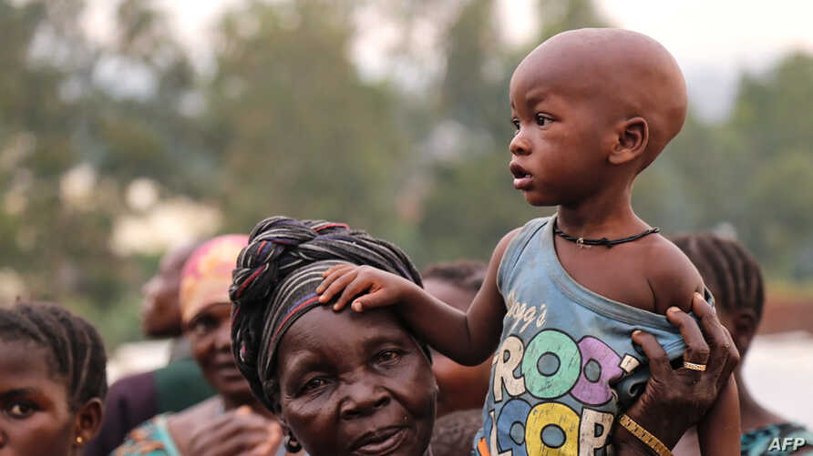 FILE - A woman holds a child on her shoulders in an internally displaced persons camp outside the town of Bunia, in Ituri province, June 21, 2019.