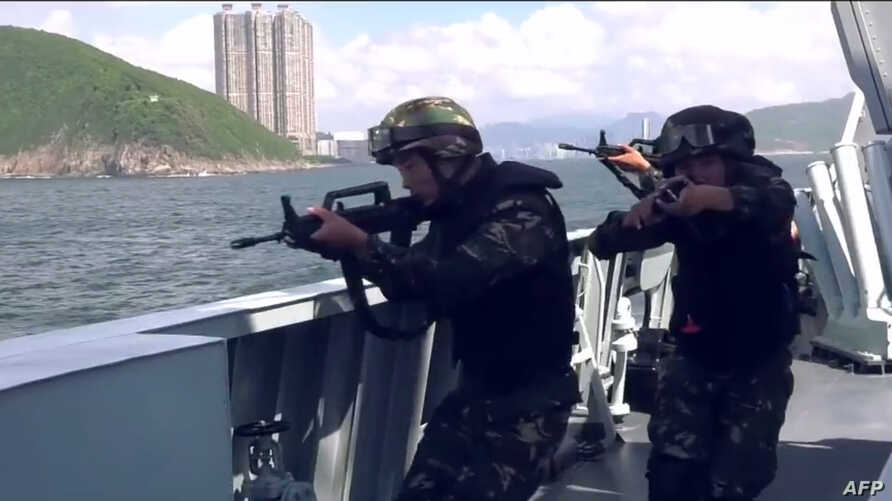 This screengrab taken from undated handout three-minute promotional video received on Aug. 1, 2019, from China's People's Liberation Army (PLA) Hong Kong Garrison shows armed PLA soldiers on a boat during a drill in Hong Kong waters.