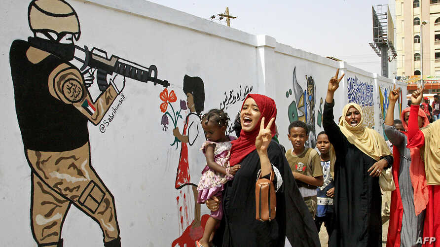 Female Sudanese demonstraters celebrate in Khartoum, Aug. 4, 2019, after Sudan's army rulers and protest leaders signed a hard-won power-sharing agreement.