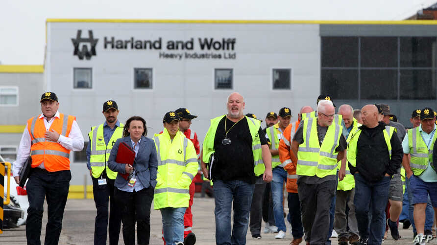 Harland and Wolff shipyard workers emerge with union reps after a meeting at the shipyard, vowing to continue their picket at the gates until their jobs are secure, in Belfast, Northern Ireland, Aug. 5, 2019.