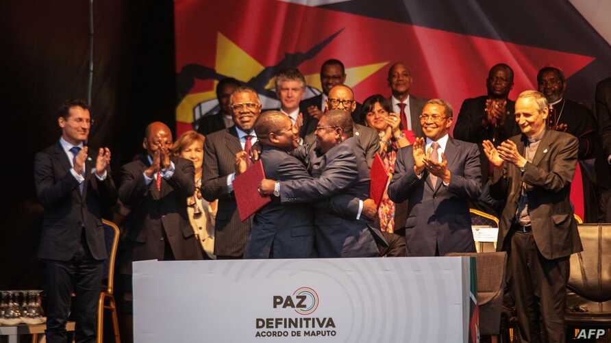 Mozambique's President Filipe Nyusi, center left, and Renamo (Mozambican National Resistence) leader Ossufo Momade hug after signing a cease-fire agreement in Maputo, Mozambique, Aug. 6, 2019.