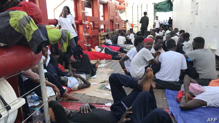 Migrants rest on the desk of the Ocean Viking rescue ship, operated by French NGOs SOS Mediterranee and Medecins sans Frontieres (MSF), during an operation in the Mediterranean Sea, Aug. 13, 2019.