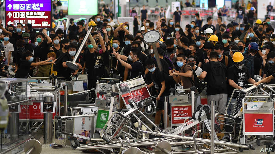 FILE - Pro-democracy protesters block the entrance to the airport terminals after a scuffle with police at Hong Kong's international airport, Aug. 13, 2019. Hundreds of flights were canceled that day as pro-democracy protesters staged a sit-in.