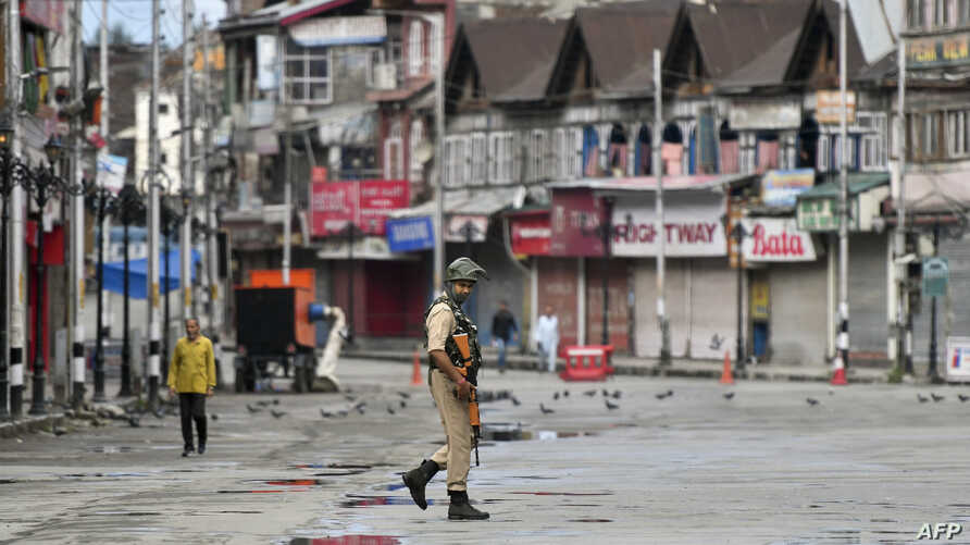 A security personnel patrols on a deserted road of the Lal Chowk area in Srinagar, Aug. 19, 2019.