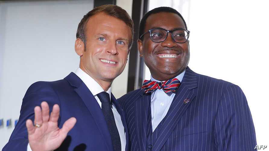 French President Emmanuel Macron, left, welcomes African Development Bank president Akinwumi Adesina upon his arrival in Biarritz, France, Aug. 25, 2019.