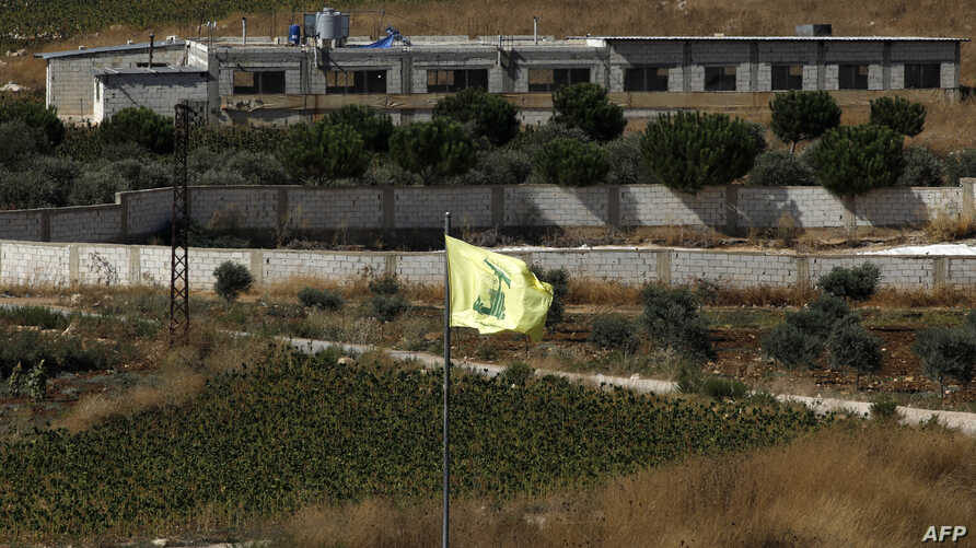 A Hezbollah flag flies in the Lebanon village of Aitaroun, near the northern Israeli town of Avivim, Aug. 26, 2019.