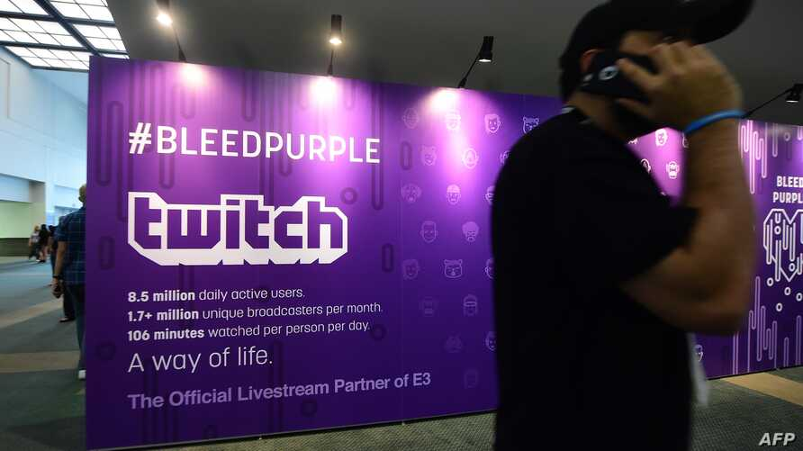 FILE - A man on his cellphone walks past an advertising board for Twitch, the official Livestream Partner of E3, during the 2016 Electronic Entertainment Expo (E3) annual video game conference and show in Los Angeles, California, June 14, 2016.