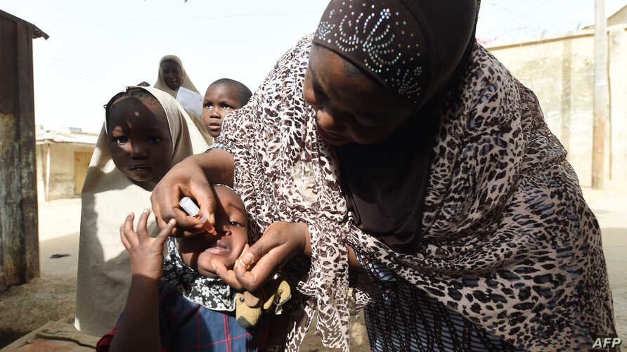 FILE - A health worker tries to immunize a child during a vaccination campaign against polio at Hotoro-Kudu, Nassarawa district of Kano, in northwest Nigeria, April 22, 2017.