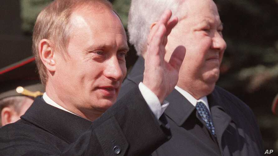 FILE - Russian President Vladimir Putin, left, waves as he stands with former President Boris Yeltsin during a parade on Red Square, in Moscow, May 9, 2000.