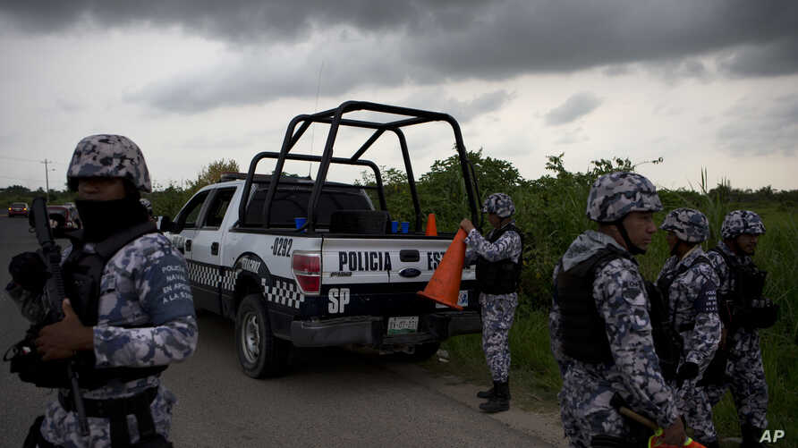 In this July 1, 2017 photo, Veracruz state police dismantle a road block in Coatzacoalcos, Mexico. Recent killings contrast with years of gangs hiding hits, recalling instead past drug wars, when criminal groups dumped piles of bodies as overt warning.