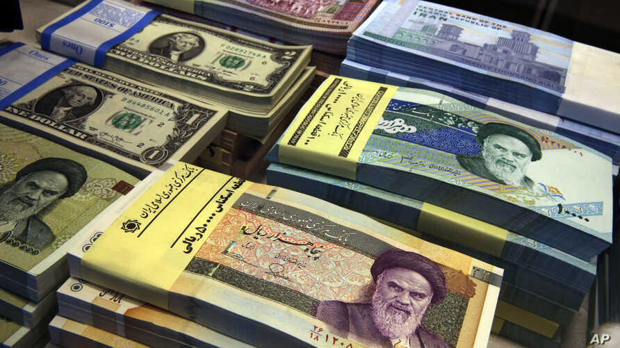 FILE - Iranian and U.S. banknotes are on display at a currency exchange shop in downtown Tehran, Iran.