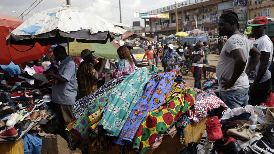 FILE - Pedestrians shop for clothes at Mokolo Market in Yaounde, Cameroon.