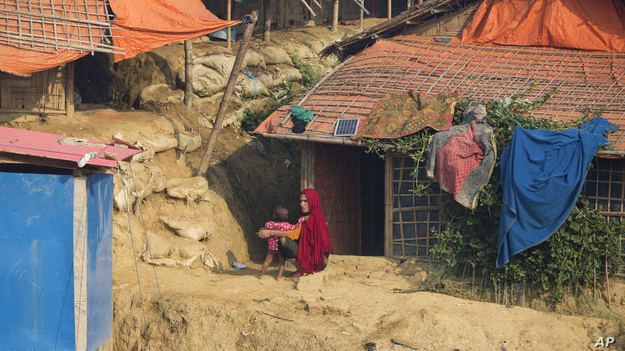 FILE - A Rohingya refugee and her child sit outside their shelter at Balukhali refugee camp near Cox's Bazar, in Bangladesh, Nov. 17, 2018.