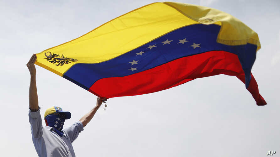 FILE - A masked anti-government protester waves a Venezuelan flag during protests in Caracas, Venezuela, May 1, 2019.