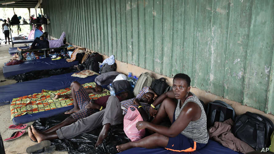 In May 10, 2019 photo, migrants from several African countries rest on mattresses outside a barn used as a shelter in Peñitas, Darien Province, Panama. African and Asian migrants tend to arrive by boat or air to Brazil, where they cross through the Amazon to Peru and turn north through Ecuador to Colombia, paying smugglers to shepherd them through the Darien Gap. (AP Photo/Arnulfo Franco)