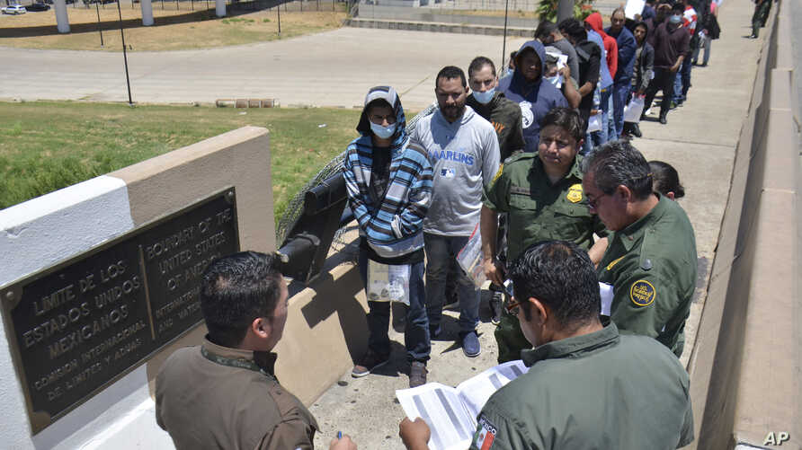 United States Border Patrol officers return a group of migrants back to the Mexico side of the border as Mexican immigration officials check the list, in Nuevo Laredo, Mexico, July 25, 2019.