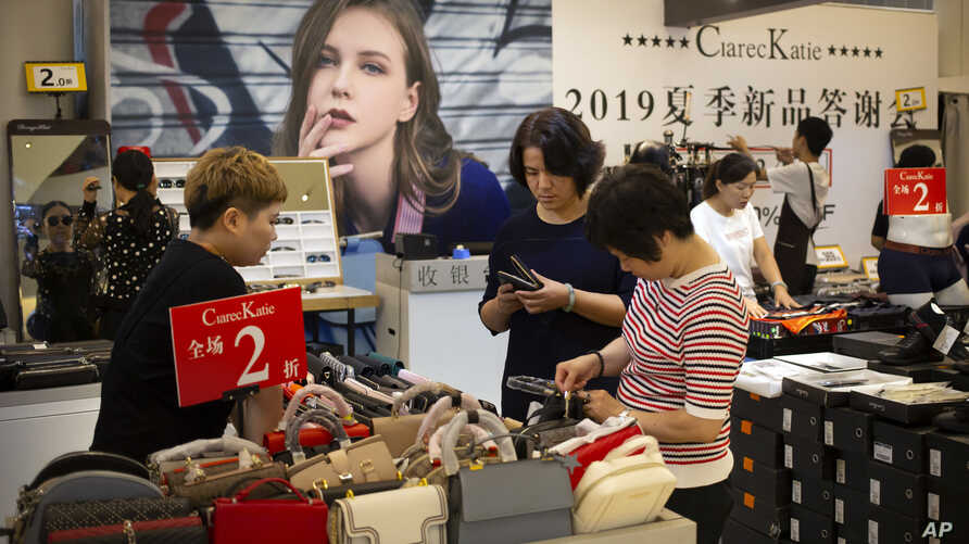 Shoppers browse at a discount retailer in a shopping mall in Beijing, Aug. 2, 2019. President Donald Trump intensified pressure on China to reach a trade deal by saying he will impose additional 10% tariffs on Sept. 1, 2019.