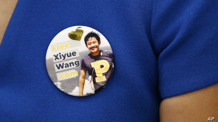 Hua Qu, the wife of Xiyue Wang, a student being held at an Iranian prison, wears a button bearing his picture as she speaks at a news conference to mark the third anniversary of his imprisonment, Aug. 8, 2019, at the National Press Club in Washington.