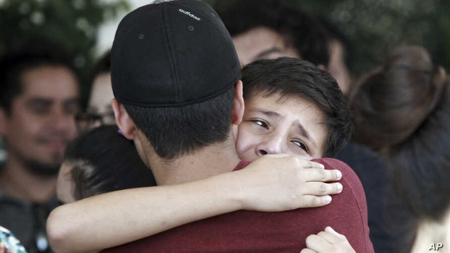 Youths comfort each other in Ciudad Juarez, Mexico, at the funeral of elementary school principal Elsa Mendoza, one of the 22 people killed in a shooting at a Walmart in El Paso, Texas, Aug. 8, 2019