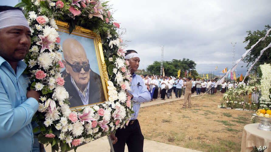 Relatives carry a portrait of former Khmer Rouge's chief ideologist and No. 2 leader, Nuon Chea, during his funeral procession in Pailin in northwestern Phnom Penh, Cambodia, Aug. 9, 2019.