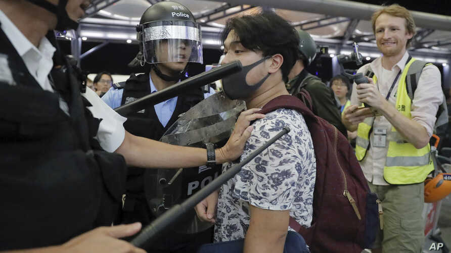 Policemen in riot gears arrest a protester during a demonstration at the Airport in Hong Kong, Aug. 13, 2019.