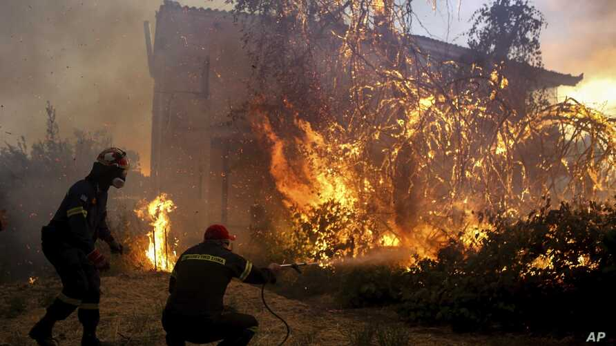 Firefighters try to extinguish flames outside a house in Agrilitsa village on the Greek island of Evia, Aug. 13, 2019.
