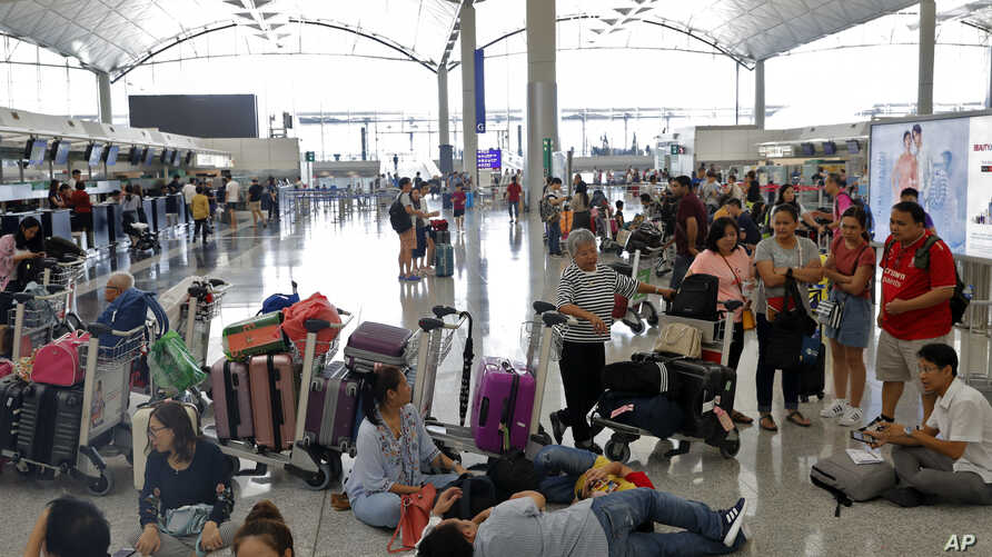 Travelers wait to check in for their flights at the airport in Hong Kong,  Aug. 14, 2019. Flights resumed at Hong Kong's airport Wednesday morning.
