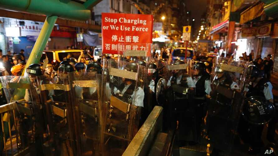 Police move out from the Shum Shui Po police station to confront protesters in Hong Kong on Wednesday, Aug. 14, 2019.