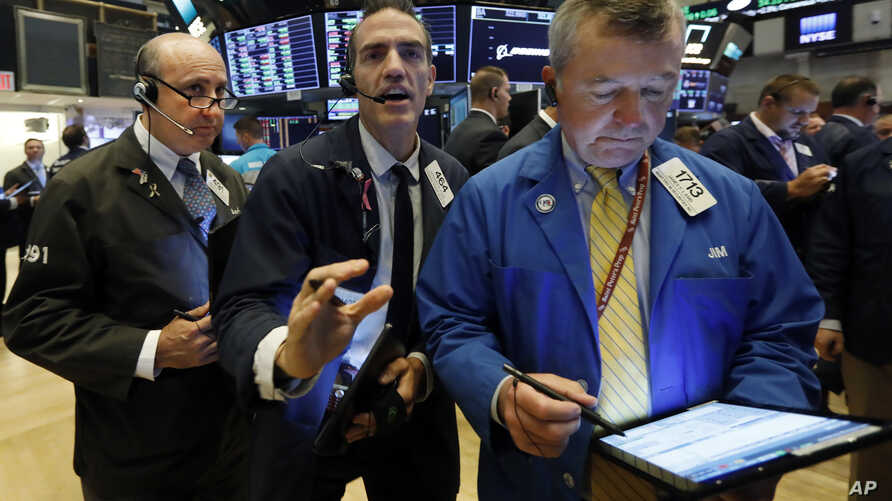 Traders Andrew Silverman, Gregory Rowe, and James Lamb, left to right work on the floor of the New York Stock Exchange, Aug. 15, 2019.
