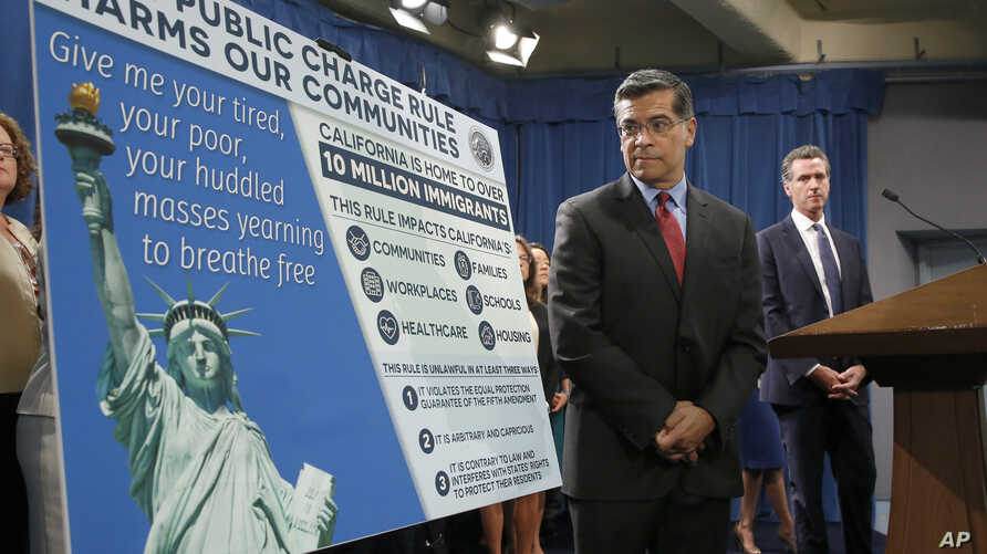 California Attorney General Xavier Becerra, left, outlines the supposed effects on immigrants under the Trump administration's new rules blocking green cards for many of those who receive government assistance, in Sacramento, Calif., Aug. 16, 2019.