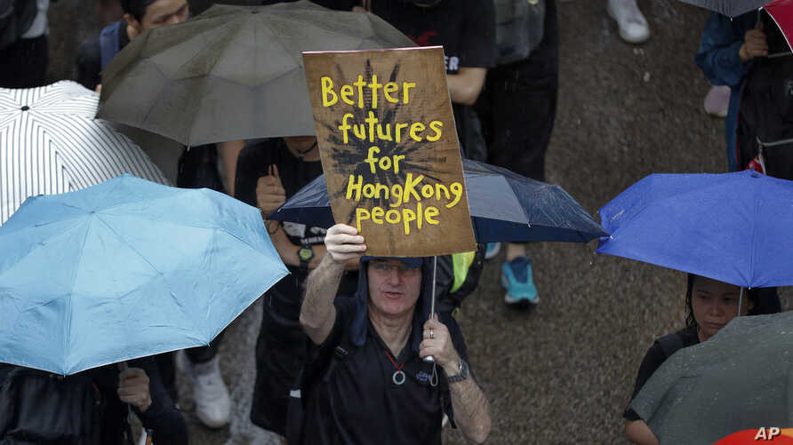 FILE - A man displays a placard as protesters gather in Hong Kong, Aug. 18, 2019.