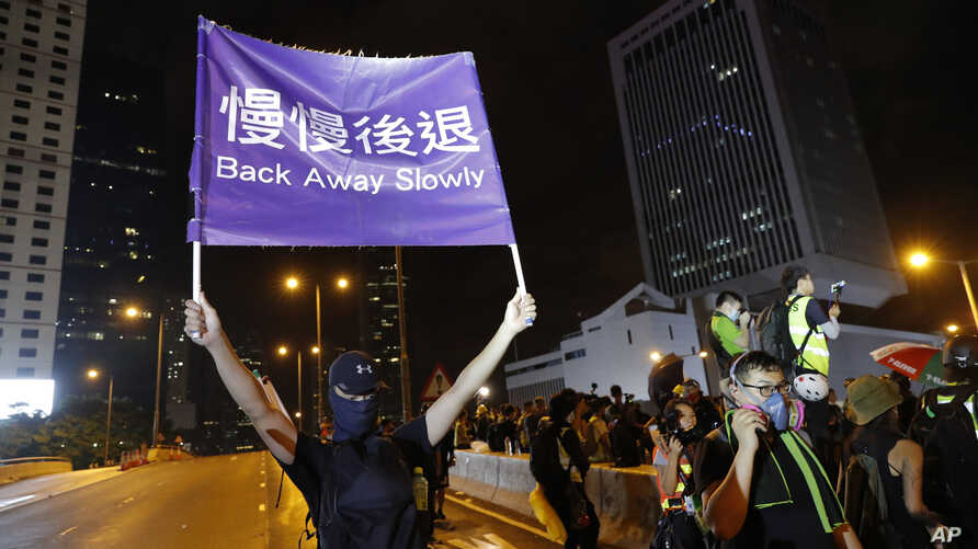 """A demonstrator holds up a sign reading """"Back away slowly"""" to encourage other demonstrators to leave, near the Chinese Liaison Office in Hong Kong, Sunday, Aug. 18, 2019."""