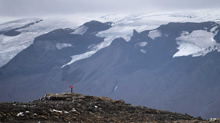 A man stops on his way to the top of what once was the Okjokull glacier, in Iceland, Sunday, Aug. 18, 2019.